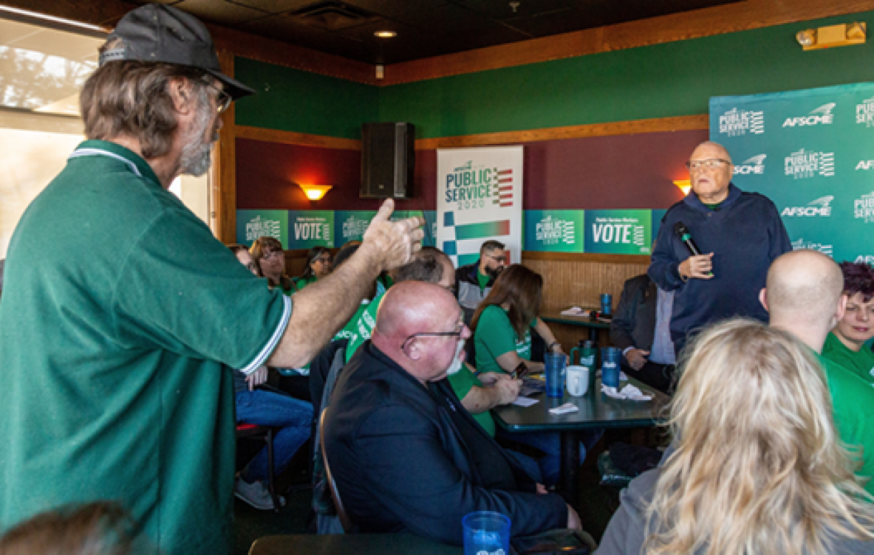 Lee Saunders speaks with an AFSCME member at an event before the Iowa caucus